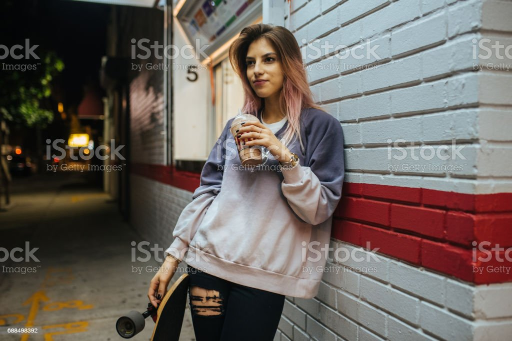 Teenage girl with longboard eating ice cream stock photo
