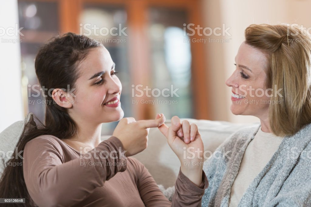 Teenage girl with mother, using sign language stock photo
