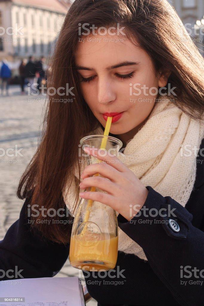 Teenage girl with orange juice in cafe stock photo
