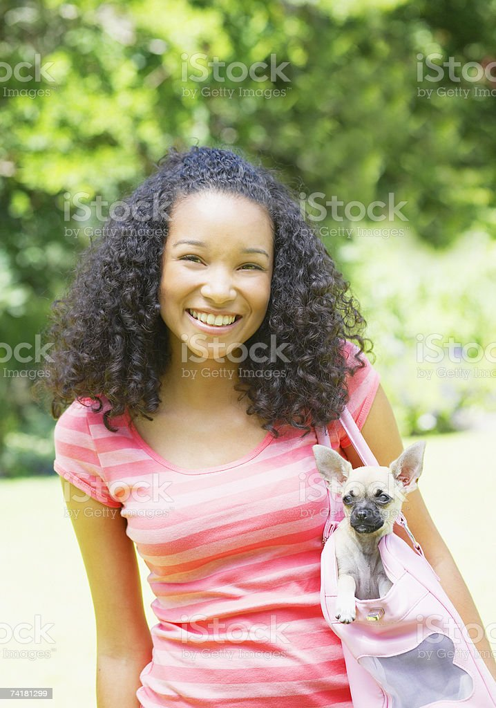 Teenage girl with puppy dog in handbag royalty-free stock photo