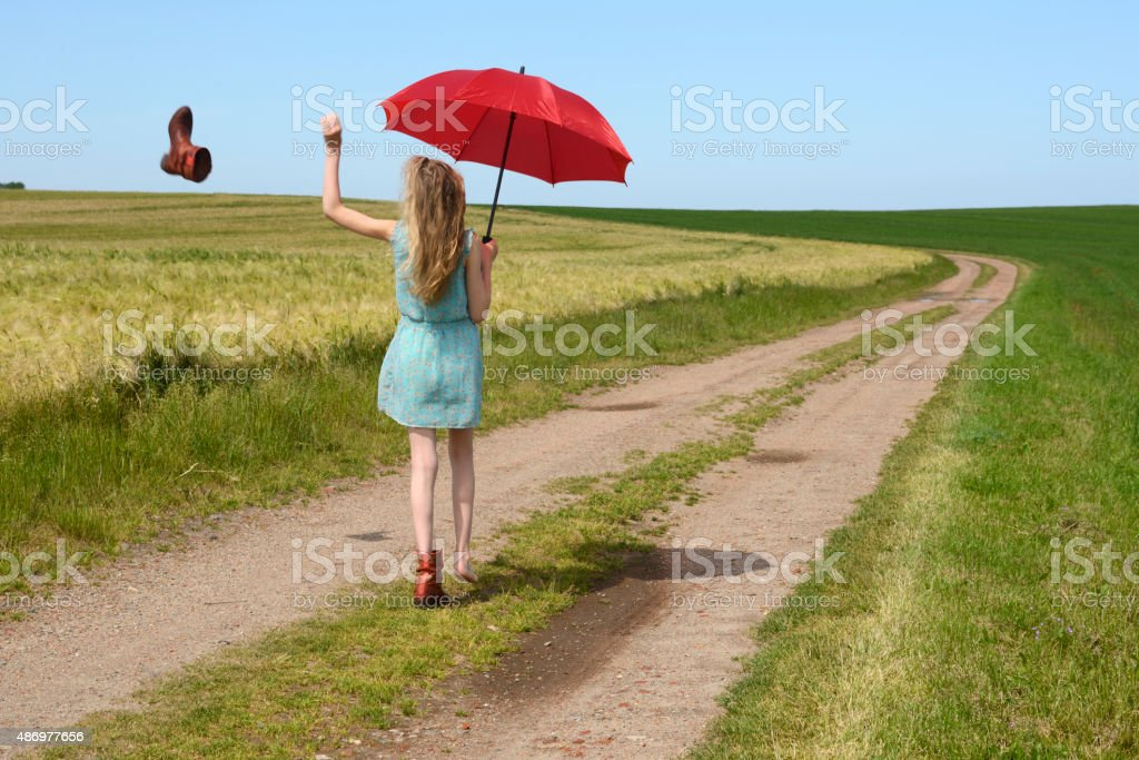 Teenage girl with red parasol walking along dirt road stock photo