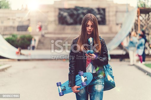 Young woman with skateboard texting on phone while walking