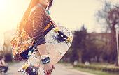Smiling girl holding skateboard outside