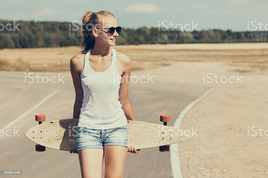 Teenage girl with skateboard stock photo