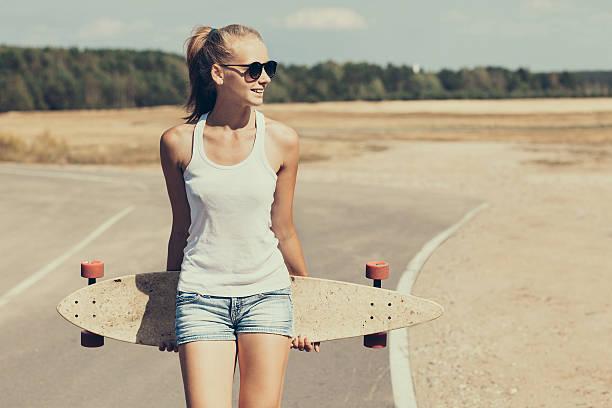 Teenage girl with skateboard stock photo