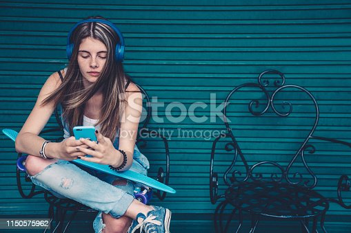 Gen Z girl sitting against colorful wall and text messaging