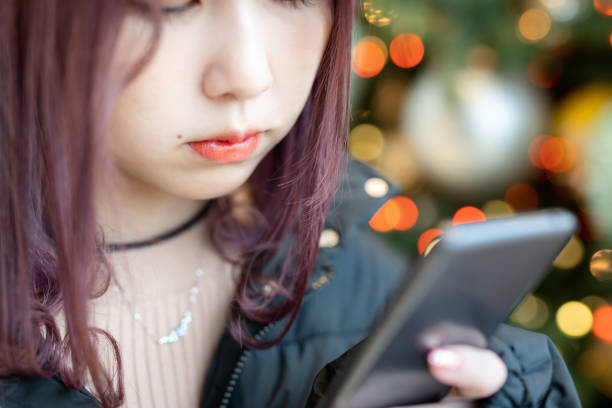 Teenage girl with smartphone standing in front of Christmas tree 17 years old Japanese girl with smartphone standing in front of Christmas tree japanese school girl stock pictures, royalty-free photos & images