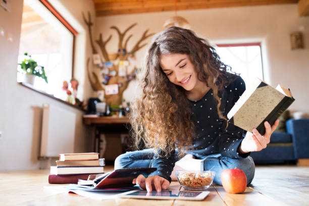 Teenage girl with tablet sitting on the floor, studying stock photo