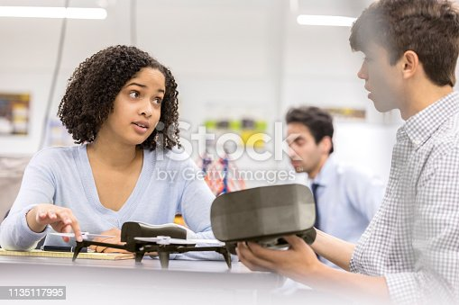 istock Teenage girl works on drone project with high school classmate 1135117995