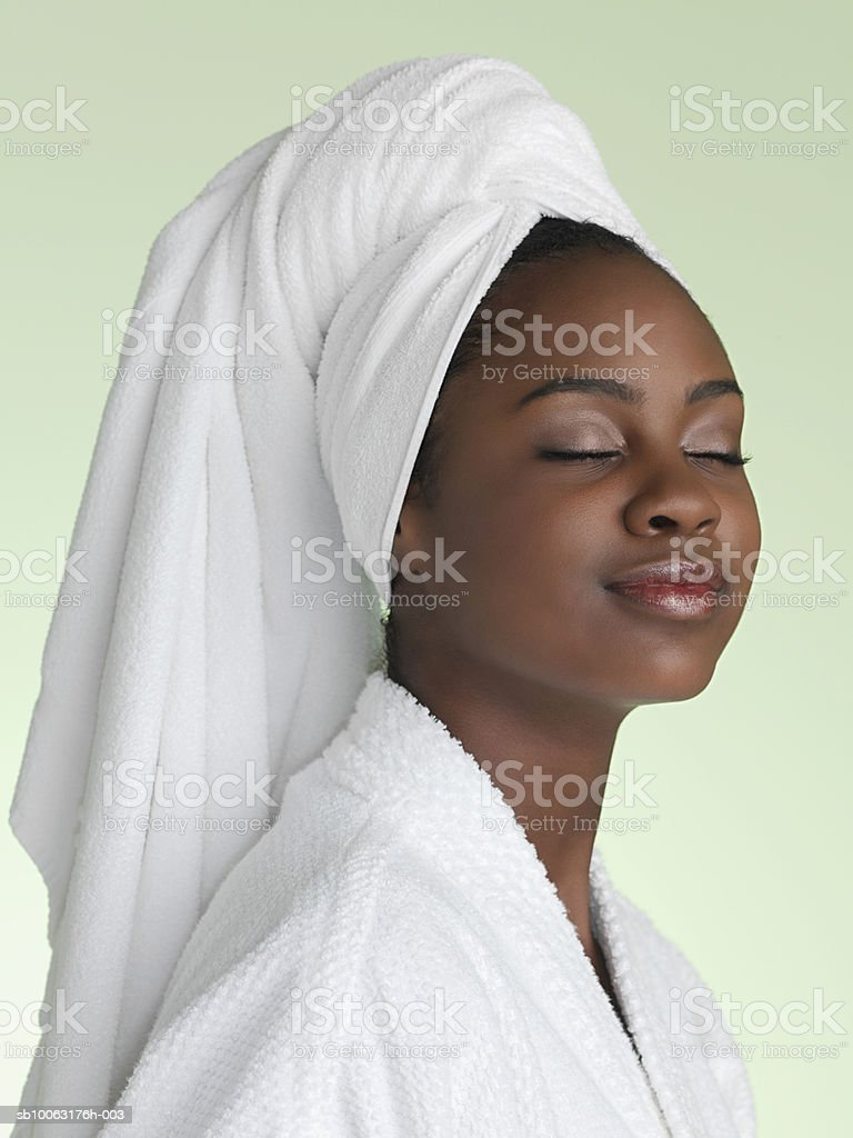 Teenage girl (16-17) wrapped in bathrobe, eyes closed, close-up royalty free stockfoto