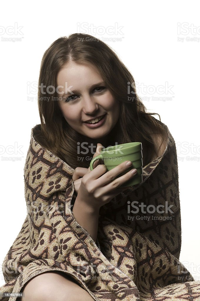 Teenage girl wrapped in blanket and holding a coffee cup royalty-free stock photo