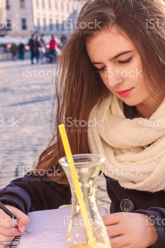 Teenage girl writing diary in cafe bar stock photo