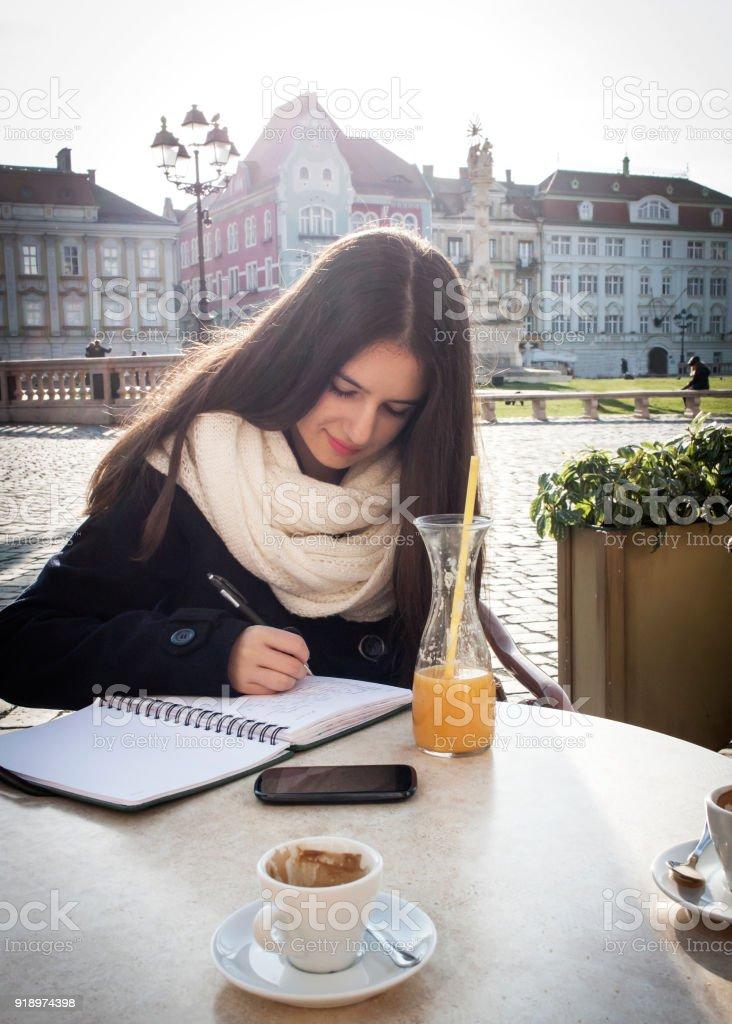 Teenage girl writing diary in cafe stock photo