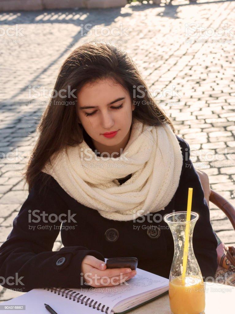 Teenage girl writing diary in coffee shop stock photo