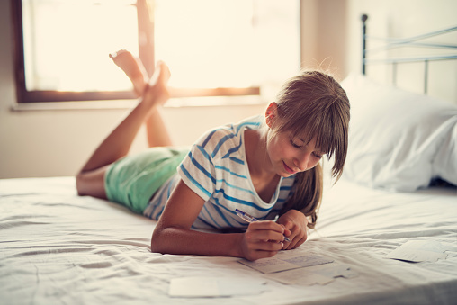 Teenage girl writing vacation postcards