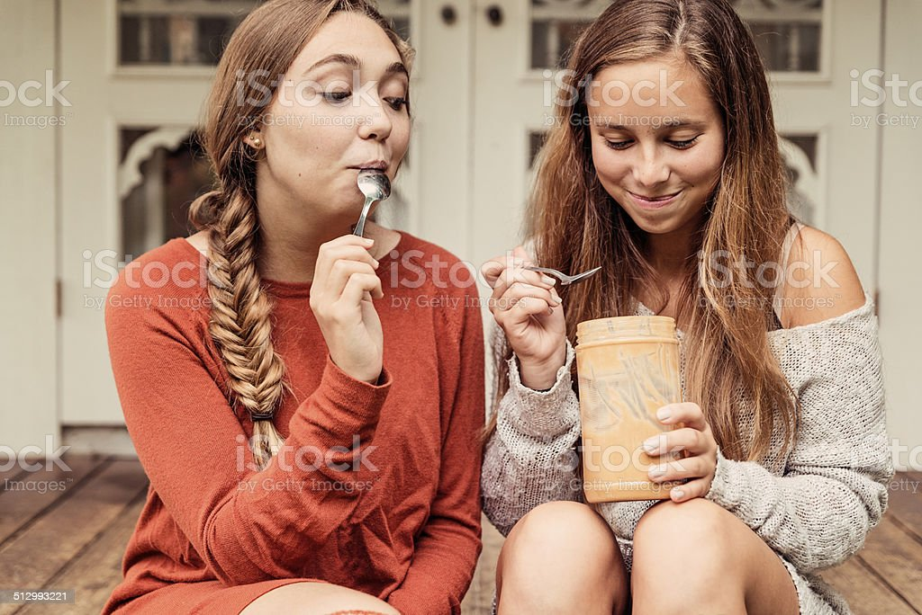 Teenage girlfriends eating peanut butter by the spoon on porch. stock photo