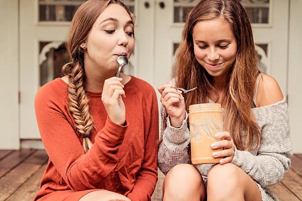 teenage girlfriends eating peanut butter by the spoon on porch. - pindakaas stockfoto's en -beelden