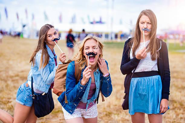teenager-mädchen in der sommer-festival mit falschen schnurrbart - schnurrbart themenpartys stock-fotos und bilder