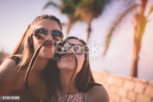 Happy teenage best friends making funny faces and hair mustaches on tropical island summer holidays