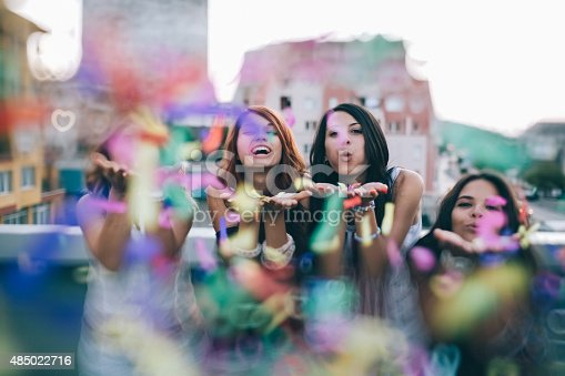 699427744 istock photo Teenage girls blowing confetti on a rooftop party 485022716