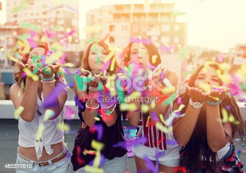 699427744 istock photo Teenage girls blowing confetti on a rooftop party 485377510