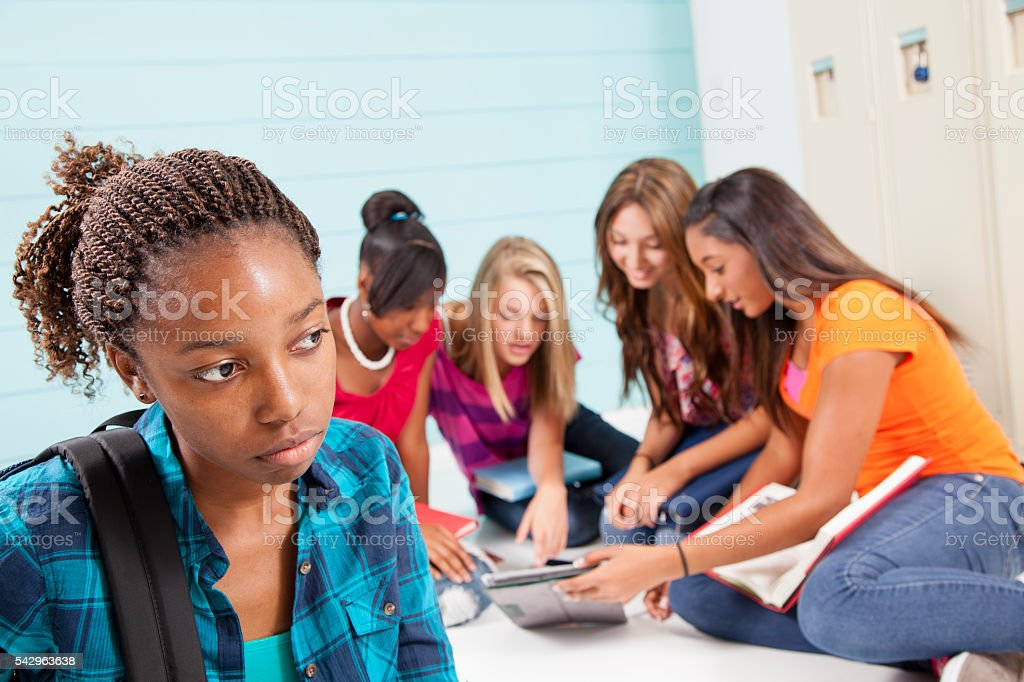 Teenage girls bully classmate. Gossip, talking. School hall. Lockers. stock photo