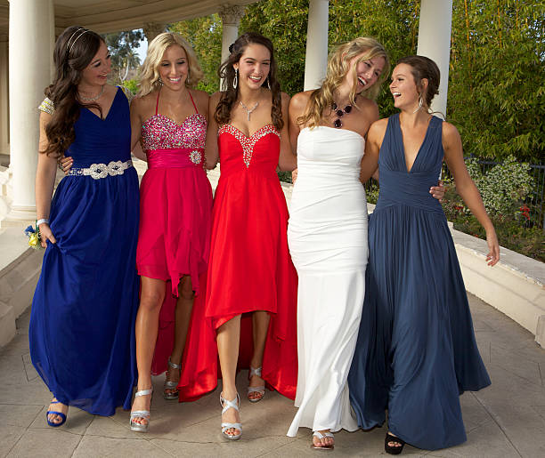 teenage girls dressed for the prom walking and having fun - prom stock photos and pictures