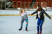 Teenage girls having fun at ice skating rink together during winter holidays