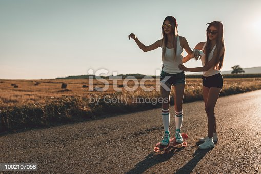 Teenage girls enjoying beautiful sunny day outdoors and driving skateboard