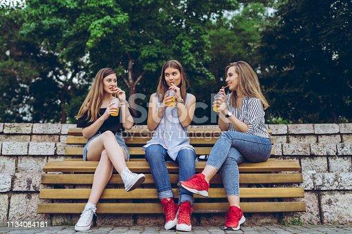 Three caucasian teenage girlfriends drinking orange juice on a bench.