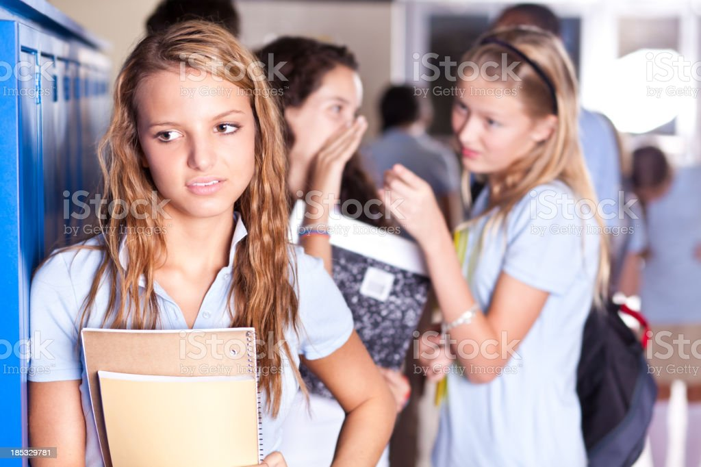Teenage girls gossiping about another teenager stock photo