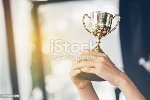 istock Teenage girls' hands are holding trophies, congratulations on success.Conception of victory in the competition. 822454888