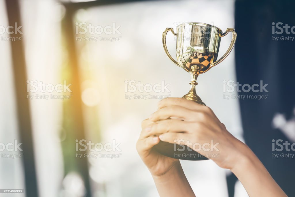Teenage girls' hands are holding trophies, congratulations on success.Conception of victory in the competition. stock photo