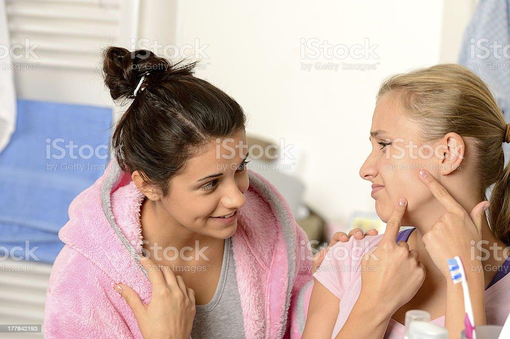 Teenage girls having acne problems in bathroom stock photo