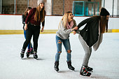 Teenage girls enjoying winter holidays and ice skating activity. Girls are having fun together