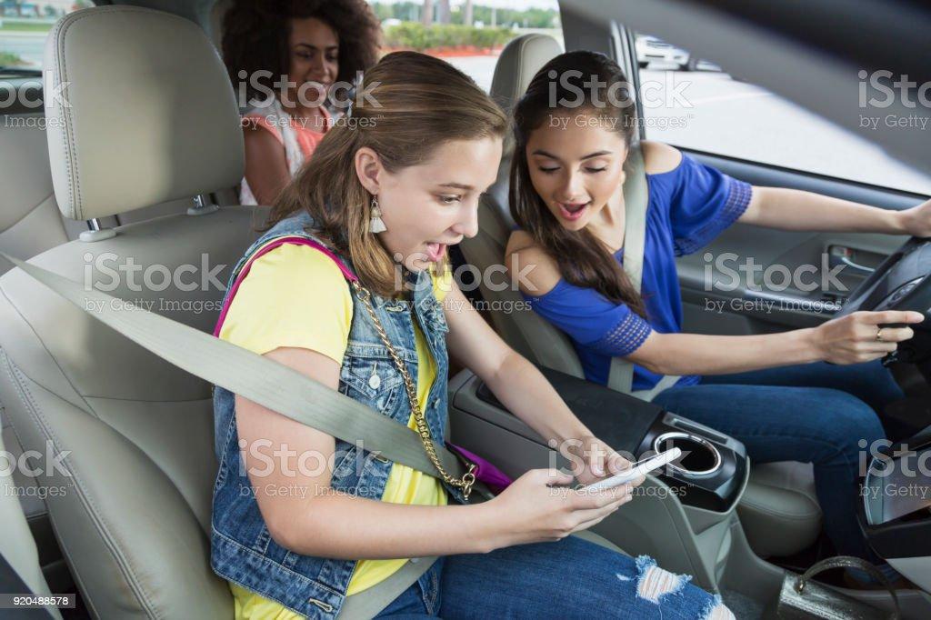 Mädchen im Teenageralter in Auto, lachen, Handy – Foto