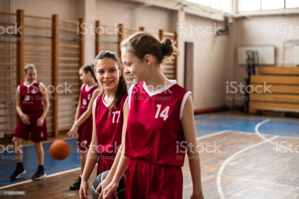 Smiling teenage girls leaving basketball field in good mood after...