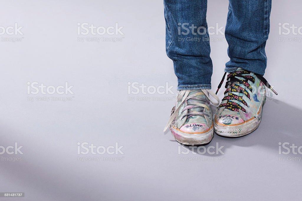Teenage Girls Legs In Worn Trainer Shoes Stock Photo