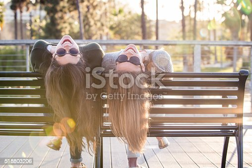 Two teenage girls goofing around on a bench at a look out in Echo Park lake in Los Angeles, California.