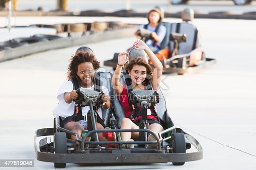 Multi-ethnic teenagers driving go carts at an amusement park.  Focus on teens in front, an African American girl and her Hispanic friend.