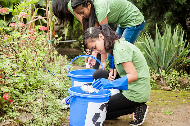 Teenage girls picking up trash to recycle. Park setting. Latin or Asian descent teenage girls picking up trash and placing in their recycling buckets.  The volunteers ares picking up garbage found on the side of a road or a local park area.  Their blue buckets have the recycling symbol on them and they wear green shirts and gloves.    social responsibility stock pictures, royalty-free photos & images