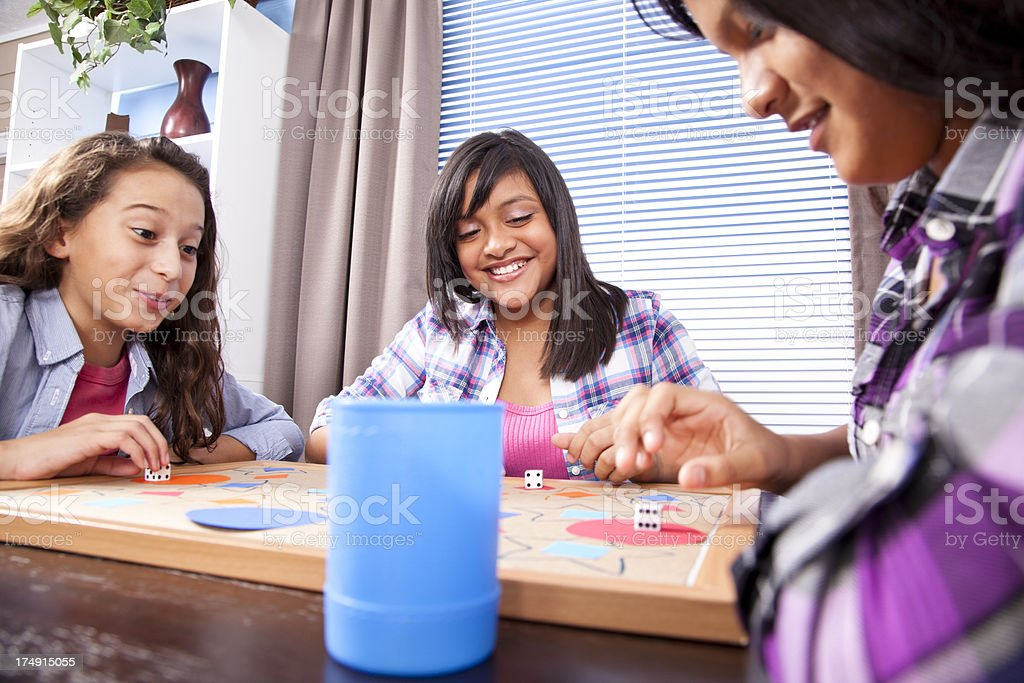Teenage girls playing a board game at home. Sisters, friends. stock photo