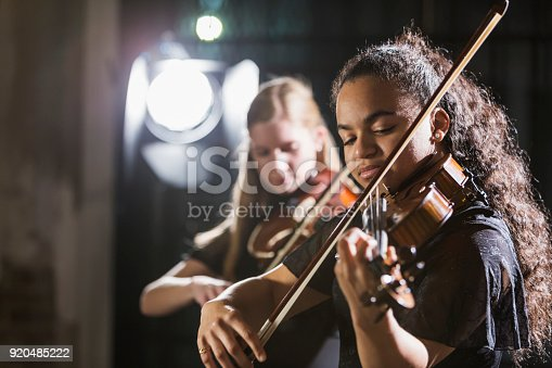 Two teenage girls playing the violin on stage. The focus is on the 15 year old mixed race girl in the foreground. She has a serious expression on her face, concentrating and looking down as she plays her instrument.