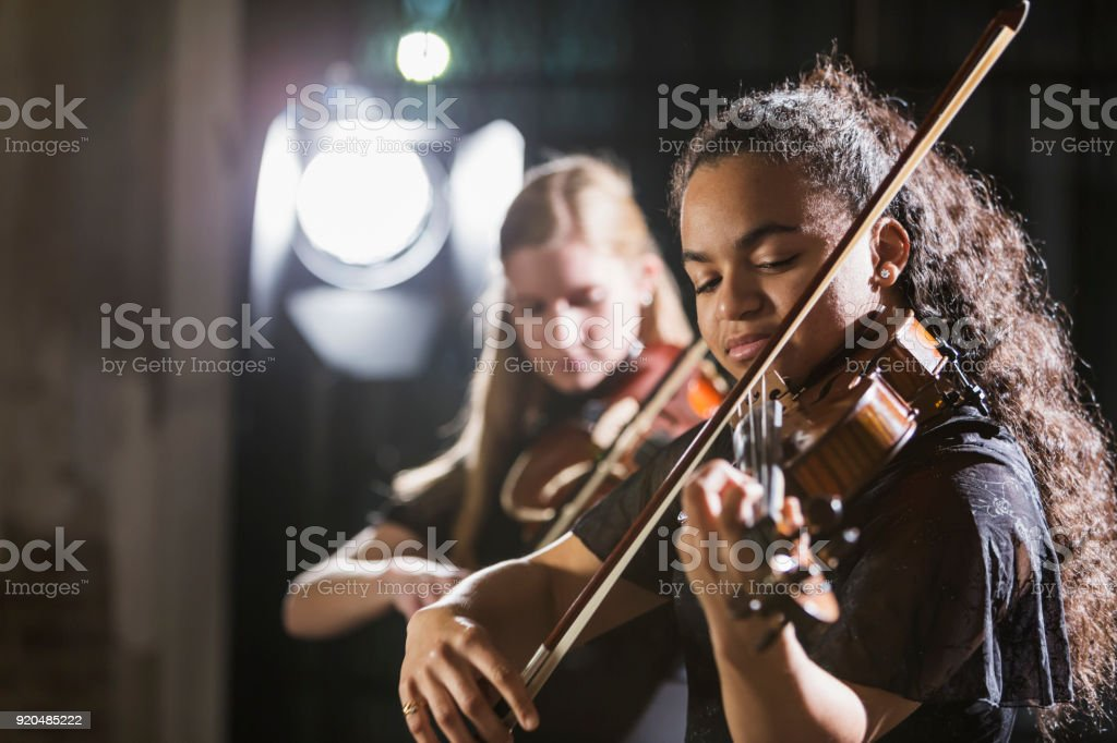Teenage girls playing violin in concert stock photo