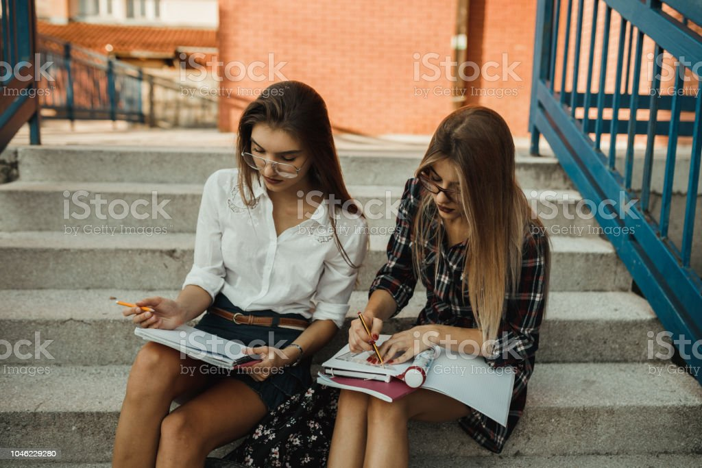 Teenage girls reading in the school playground stock photo