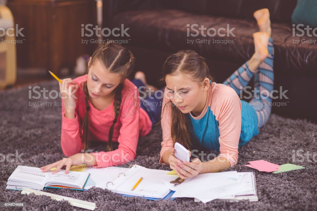 Teenage girls reading together on couch stock photo