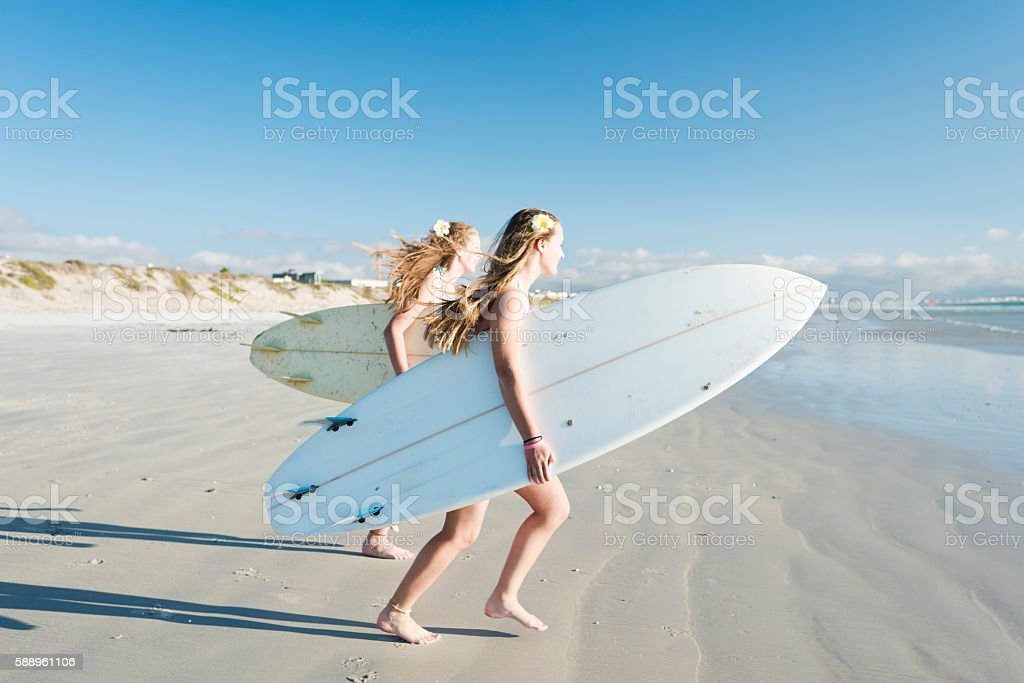 Teenage Girls Running Towards The Ocean With Their Surfboards - foto de stock