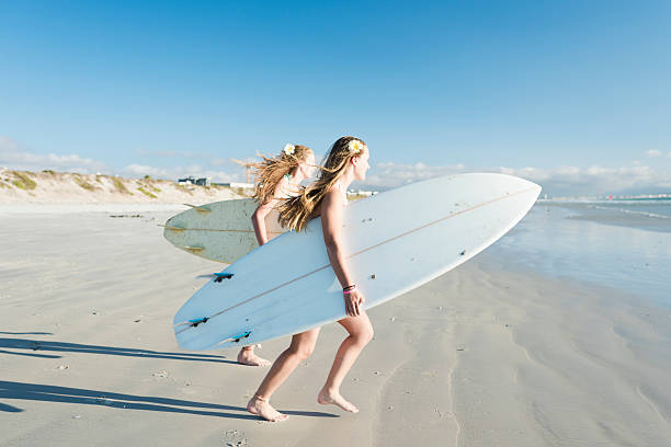 Teenage Girls Running Towards The Ocean With Their Surfboards stock photo