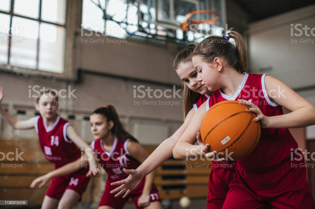 Skillful Teenage girls practicing defensive game at basketball...