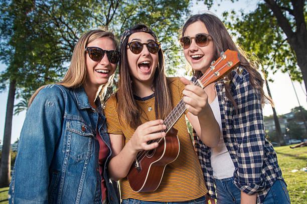 junge mädchen singen im park - ukulele songs stock-fotos und bilder